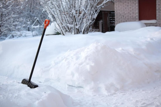 A shovel rests in a snowbank after being used to remove the snow from the sidewalk.