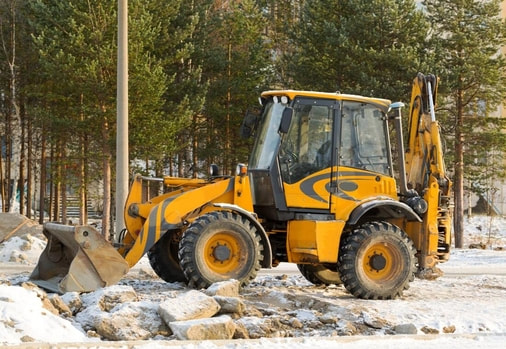 A loader is parked at a job site after being used to clear the land for construction.